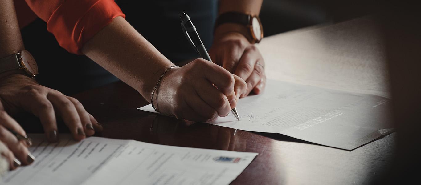 Käsi allekirjoittaa paperia